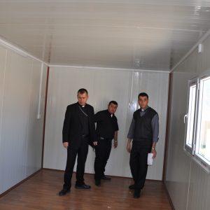 Mitarbeiter der Caritas inspizieren vor Ort einen Wohncontainer